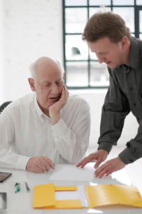 standing younger man explaining paper work to seated older man